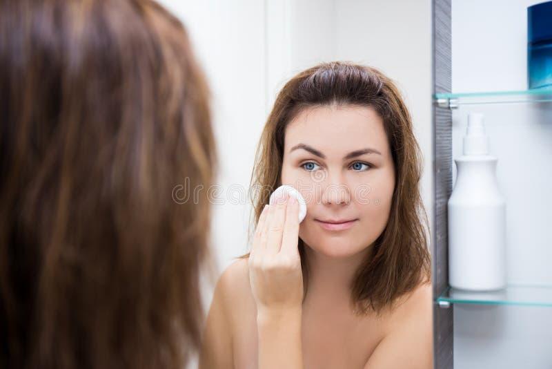 Ung kvinna som tvättar hennes framsida med lotion i badrum arkivfoton