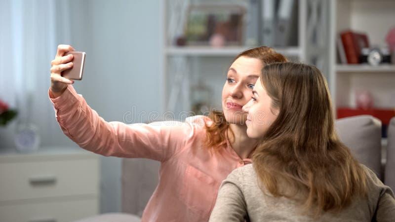 Ung kvinna som två tar selfie vid smartphonen, kvinnlig vänfritid, teknologi fotografering för bildbyråer