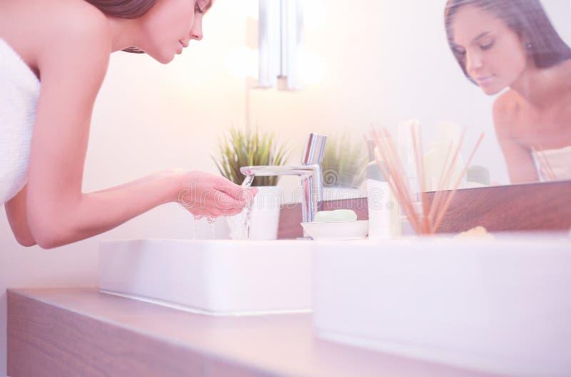 Ung kvinna som tv?ttar hennes framsida med rent vatten i badrum fotografering för bildbyråer