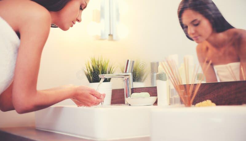 Ung kvinna som tv?ttar hennes framsida med rent vatten i badrum royaltyfri foto