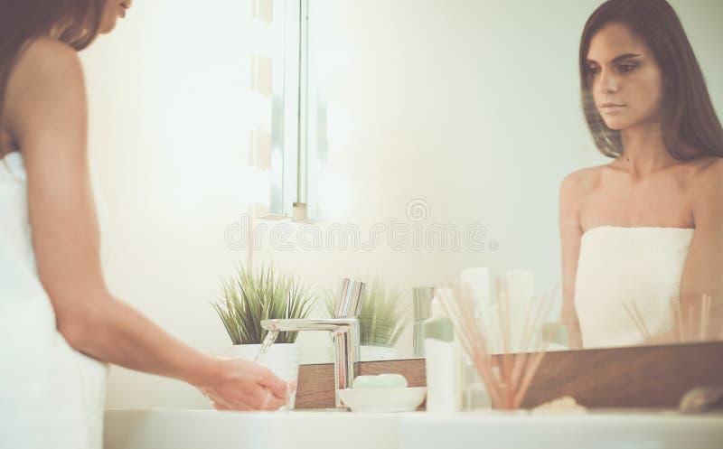 Ung kvinna som tv?ttar hennes framsida med rent vatten i badrum royaltyfria bilder