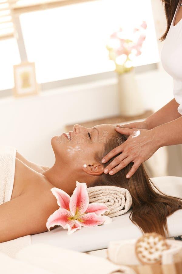 Ung kvinna som tycker om ansikts- massage royaltyfri bild