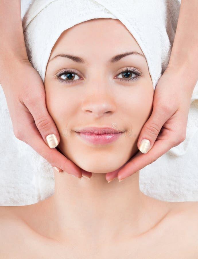 Ung kvinna som tycker om ansikts- massage i brunnsort arkivbild