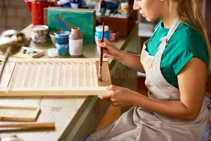 Ung kvinna som tycker om att tillverka i studio royaltyfria bilder