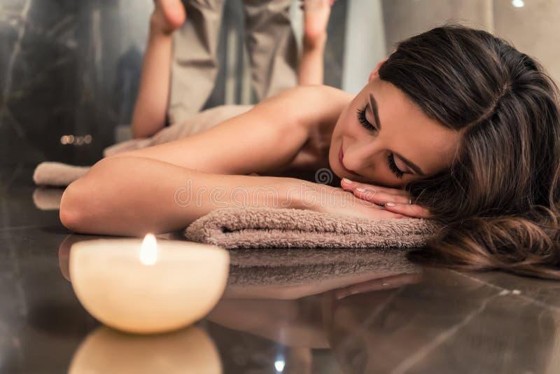 Ung kvinna som tycker om de sträckande teknikerna av den thailändska massagen royaltyfria bilder