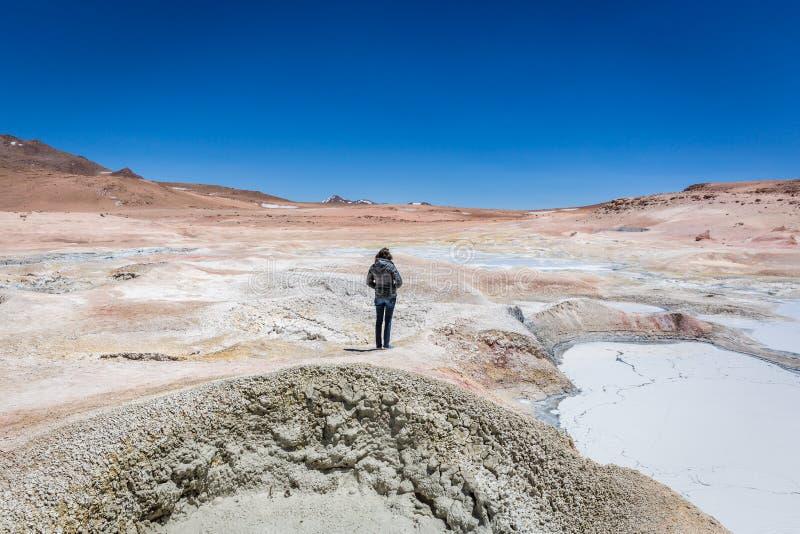 Ung kvinna som tycker om den fantastiska geyseren av Bolivia Altiplano, mellan Chile och Bolivia, meter för mer än 5 tusentals ov fotografering för bildbyråer