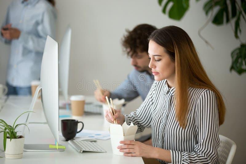 Ung kvinna som tycker om den kinesiska matasken under kontorslunchavbrott arkivbild