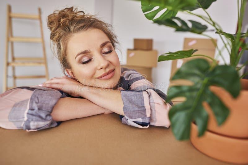 Ung kvinna som tycker om den nya lägenheten royaltyfri bild