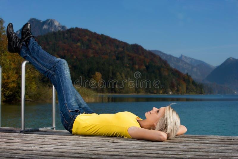 Ung kvinna som tycker om en avslappnande dag på sjön arkivbild