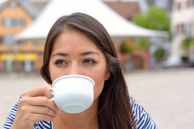 Ung kvinna som tycker om en kopp kaffe eller ett te royaltyfri fotografi