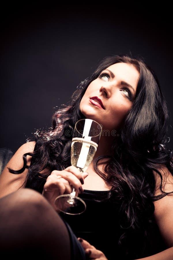 Ung kvinna som tycker om ett exponeringsglas av Champagne arkivfoto