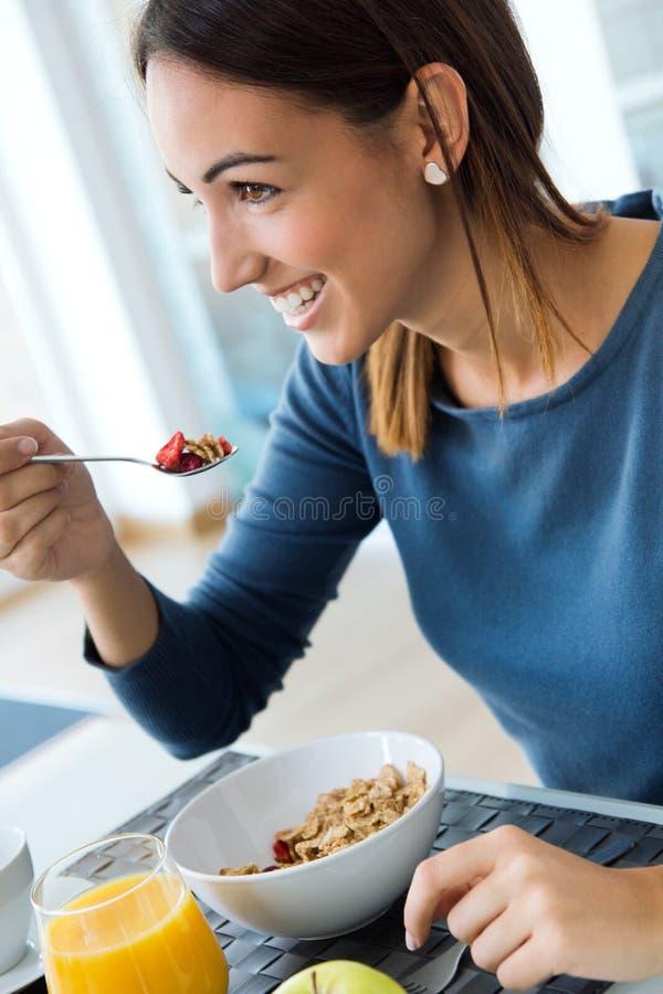 Ung kvinna som tycker om frukosten i köket royaltyfri foto