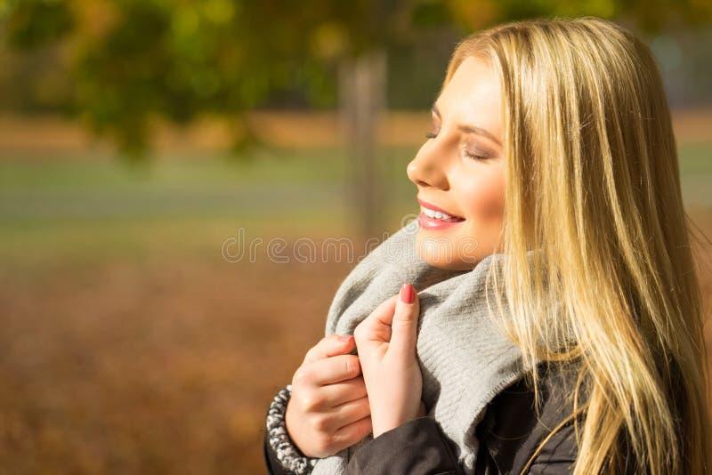 Ung kvinna som tycker om höstsolen royaltyfri bild
