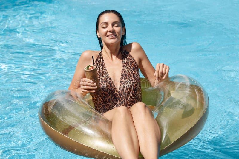 Ung kvinna som tycker om hennes lyxiga semester på semesterorten och att simma med gummicirkeln och coctailen i hand i simbassäng arkivbild