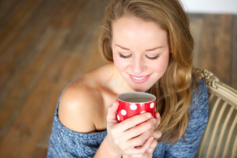 Ung kvinna som tycker om kopp te hemma royaltyfri bild
