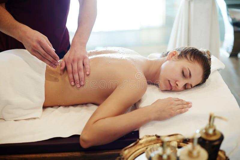 Ung kvinna som tycker om massage i brunnsort arkivbilder