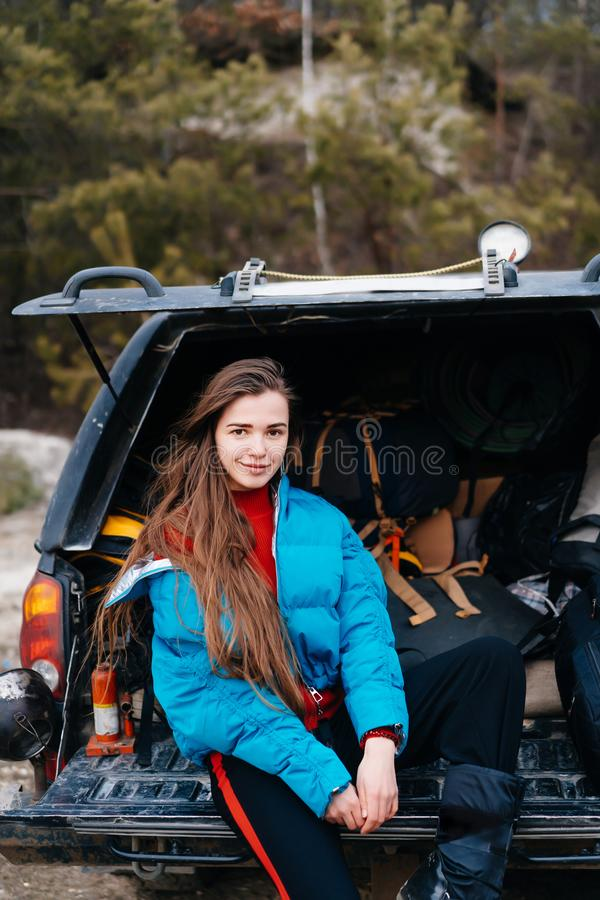 Ung kvinna som tycker om naturen, medan sitta i bilstammen royaltyfria foton