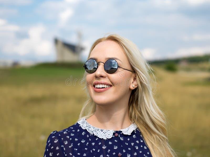 Ung kvinna som tycker om naturen och solljus i sugrörfält arkivbilder