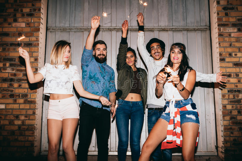 Ung kvinna som tycker om partiet med hennes vänner royaltyfria foton
