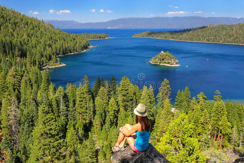 Ung kvinna som tycker om sikten av Emerald Bay på Lake Tahoe, Cali arkivfoto
