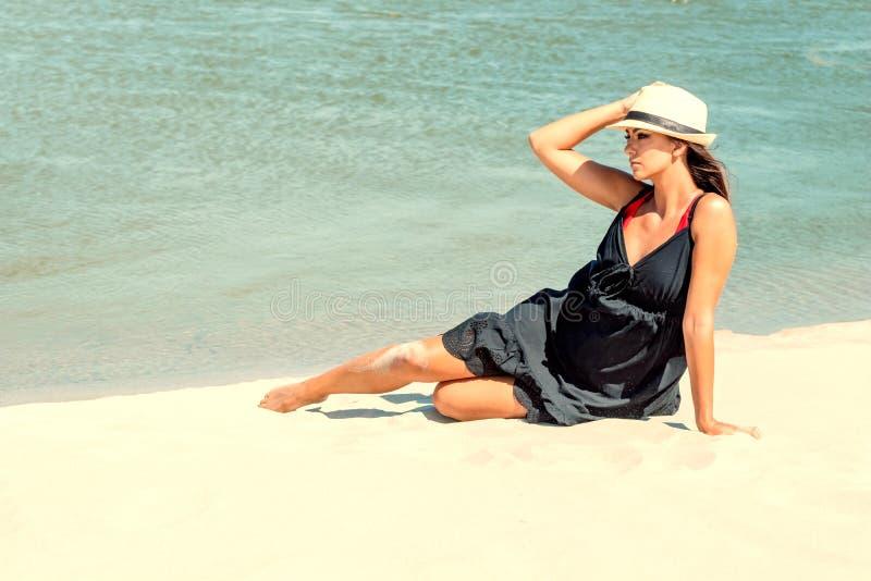 Ung kvinna som tycker om solig dag på den tropiska stranden royaltyfri foto
