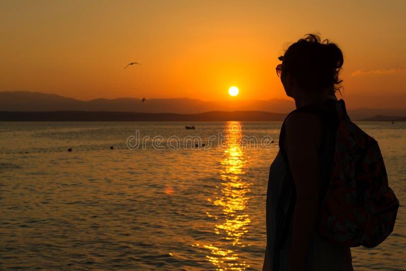 Ung kvinna som tycker om solnedgång arkivfoton