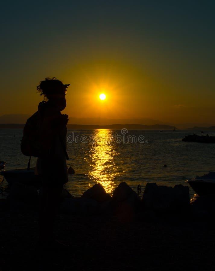Ung kvinna som tycker om solnedgång arkivbild