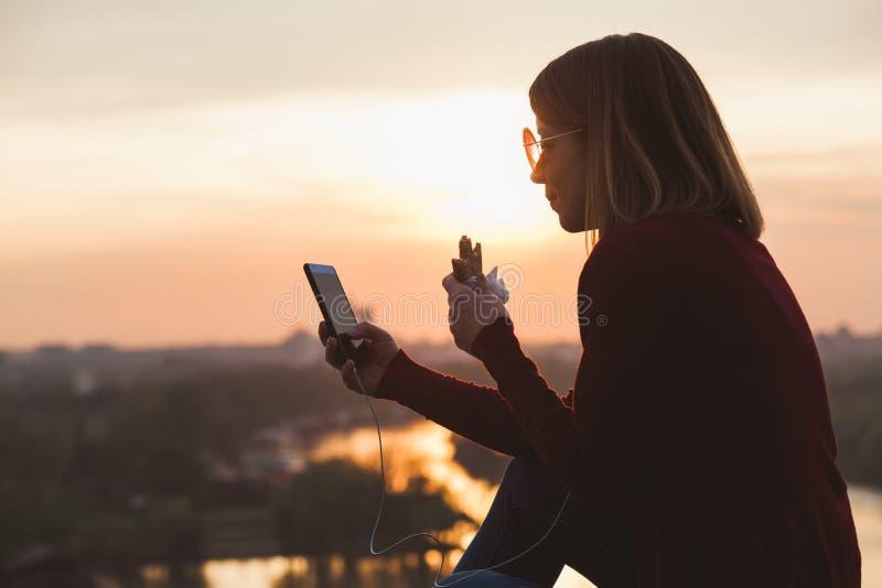 Ung kvinna som tycker om solnedgången som lyssnar till musiken och har ett mellanmål arkivfoto