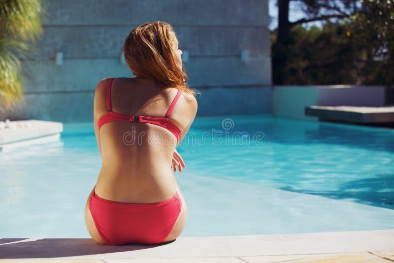 Ung kvinna som tycker om sommar på simbassängen arkivbilder