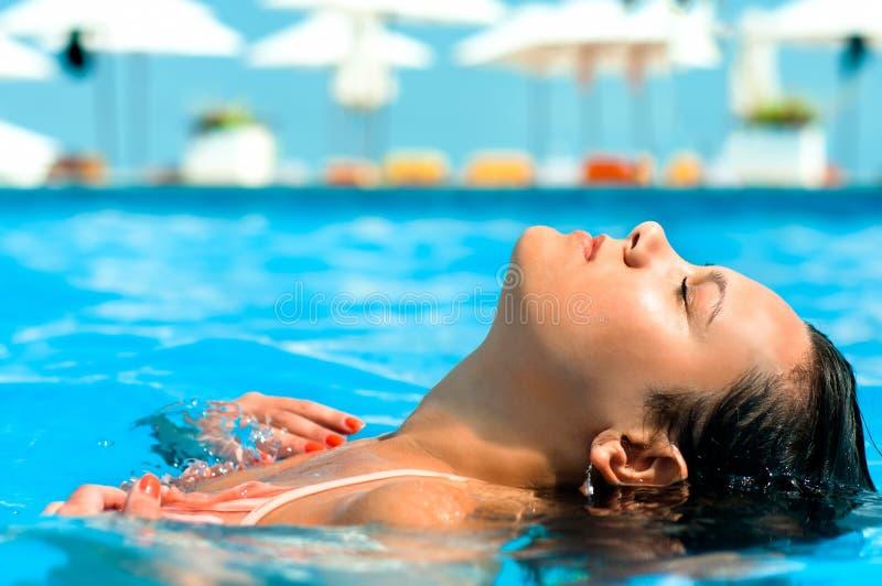 Ung kvinna som tycker om vatten och solen i utomhus- simbassäng royaltyfri bild