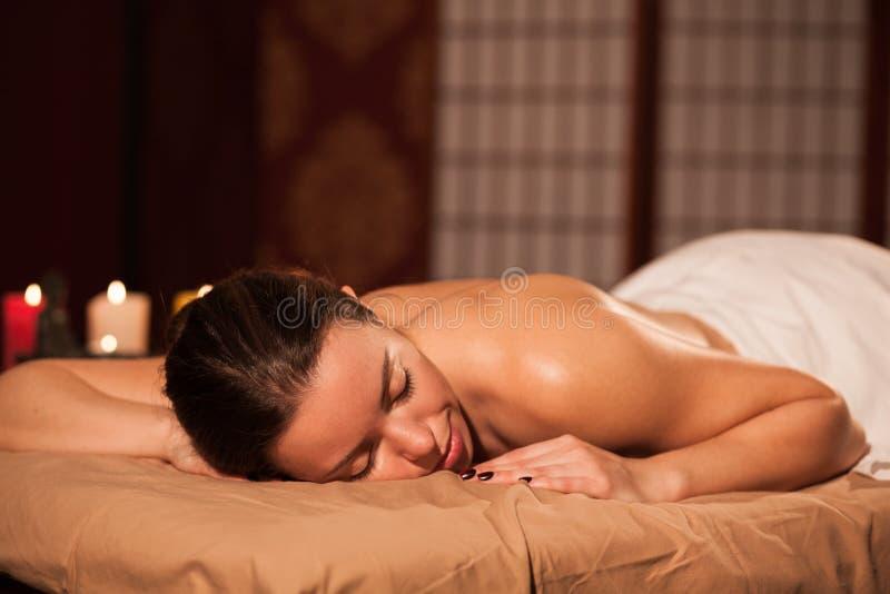 Ung kvinna som tycker om yrkesmässig massage arkivfoto