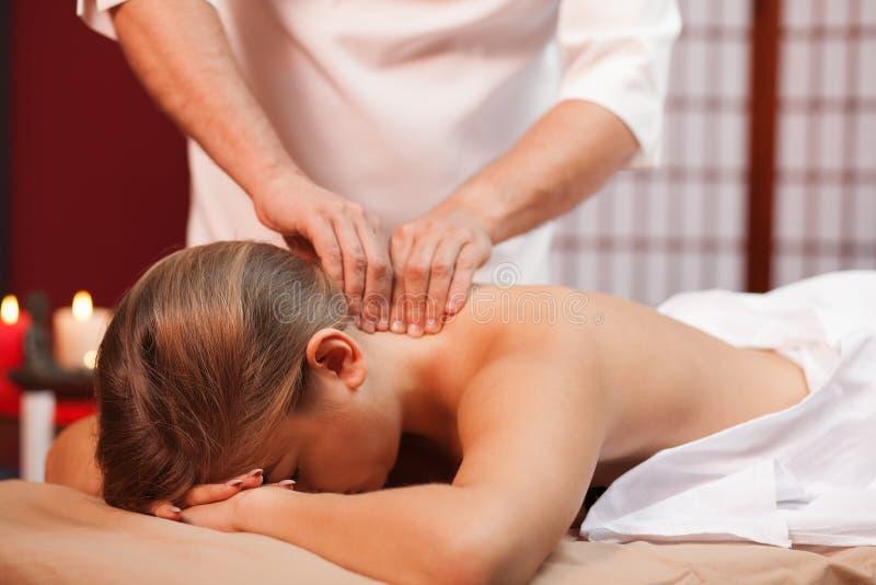 Ung kvinna som tycker om yrkesmässig massage arkivbild