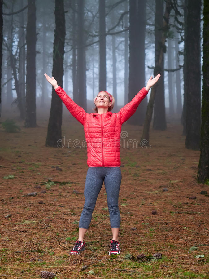 Ung kvinna som undersöker bedöva den dimmiga skogen för höst royaltyfria bilder