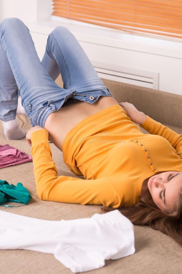 Ung kvinna som upp klär jeans på soffan royaltyfria foton