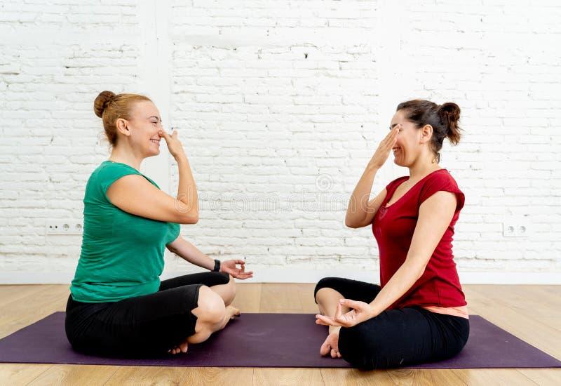 Ung kvinna som upprepar yoga som andas övning efter hennes yogilärare i idrottshall i sund livsstil fotografering för bildbyråer