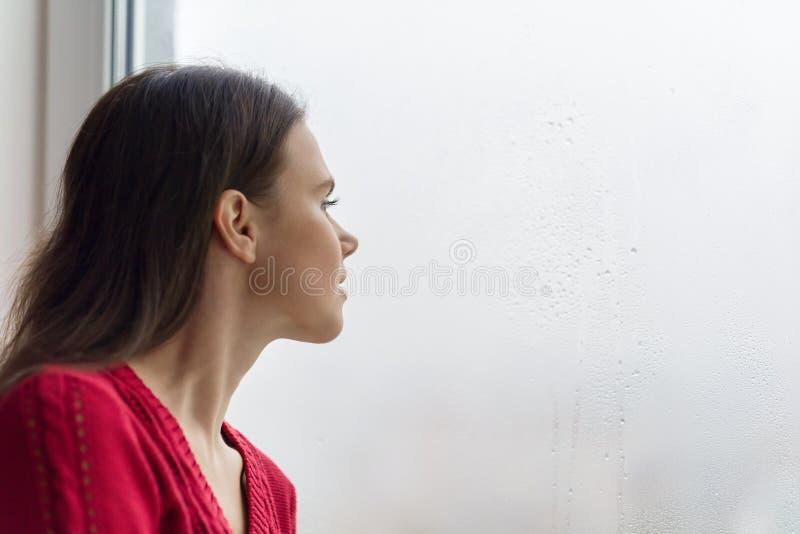 Ung kvinna som ut ser fönstret på en regnig dag, kopieringsutrymme royaltyfri bild