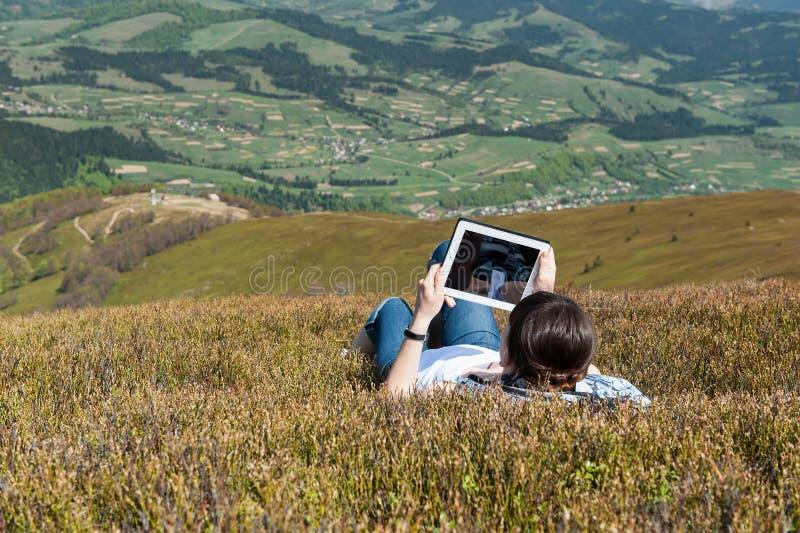 Ung kvinna som utomhus använder minnestavladatoren arkivbild