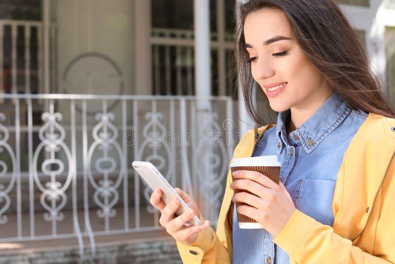 Ung kvinna som utomhus använder telefonen royaltyfri bild