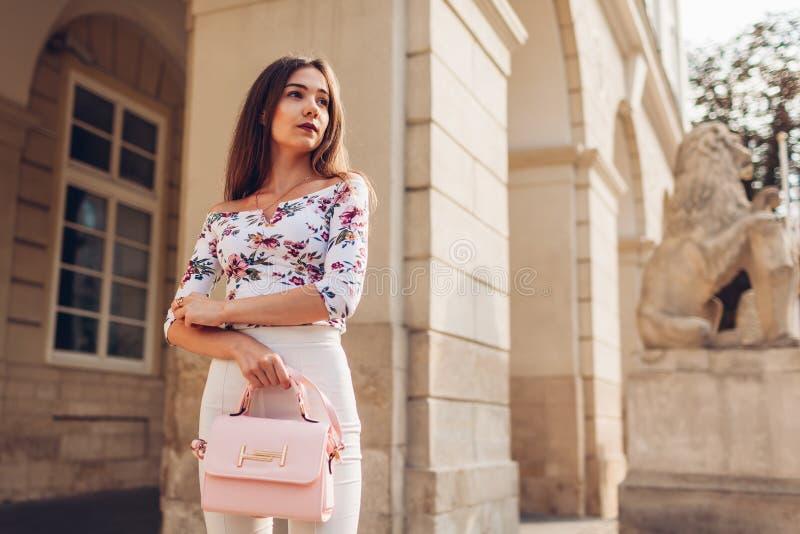 Ung kvinna som utomhus bär den härliga dräkten och tillbehör och skor Flicka som rymmer den stilfulla handväskan guld- modell för arkivbilder