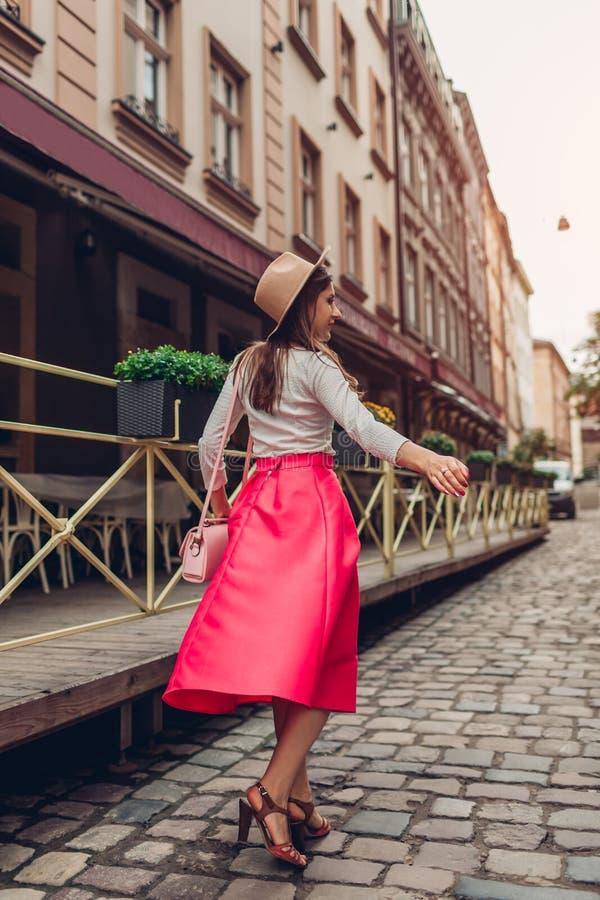 Ung kvinna som utomhus bär stilfulla kläder och tillbehör Modellera att gå på den tomma stadsgatan i hatt arkivbild