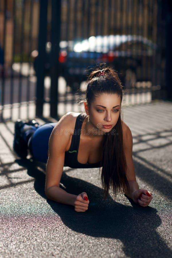Ung kvinna som utomhus gör plankan royaltyfria foton