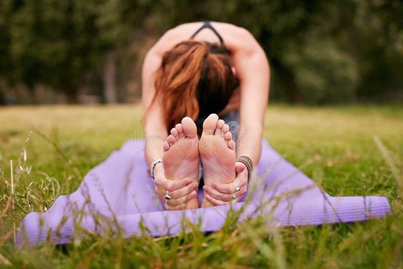 Ung kvinna som utomhus gör yoga på gräs royaltyfria foton