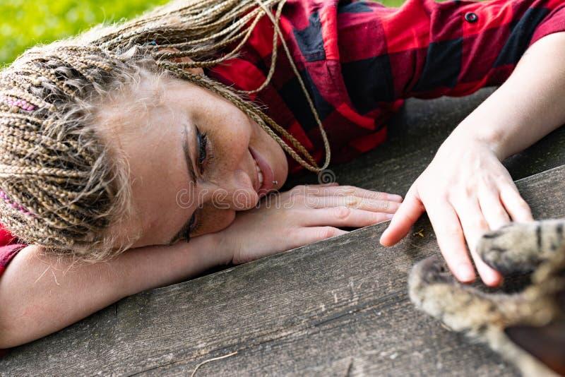 Ung kvinna som utomhus kopplar av med hennes husdjurkatt arkivbilder