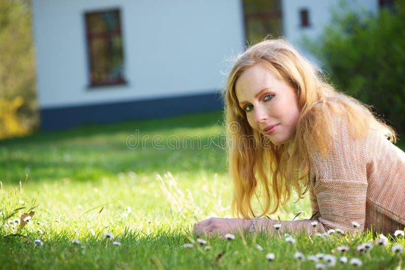 Ung kvinna som utomhus kopplar av på gräs arkivfoto