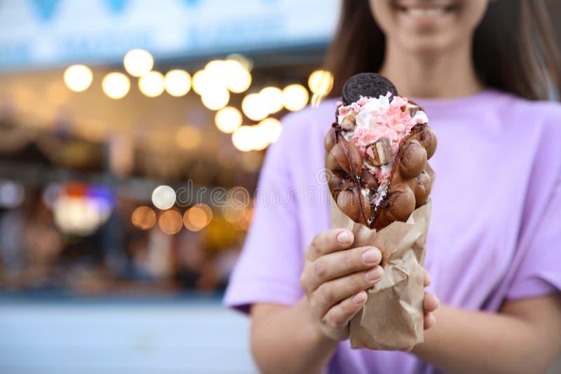 Ung kvinna som utomhus rymmer den läckra bubbladillanden med glass, closeup arkivfoton