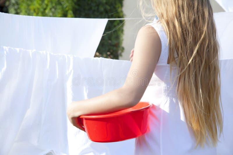 Ung kvinna som utomhus torkar den rena tvätterit i rep Flickatonåring med handfatet i händer arkivfoto