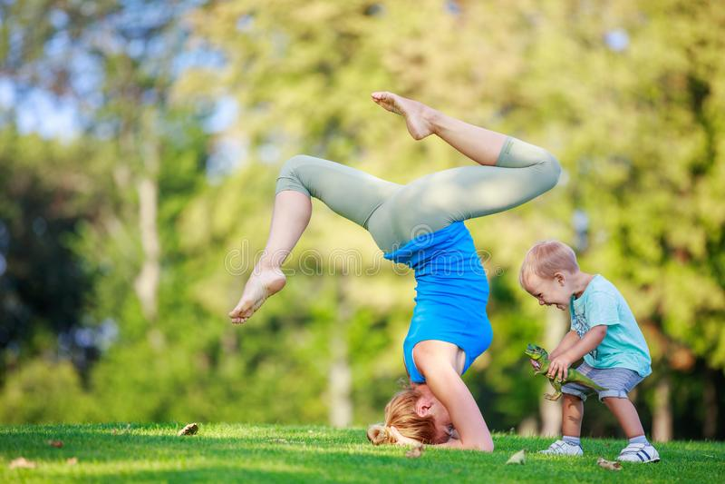 Ung kvinna som utomhus utarbetar, liten son som spelar bredvid henne royaltyfria foton