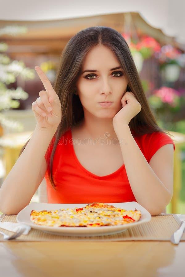 Ung kvinna som vägrar att äta en pizza fotografering för bildbyråer