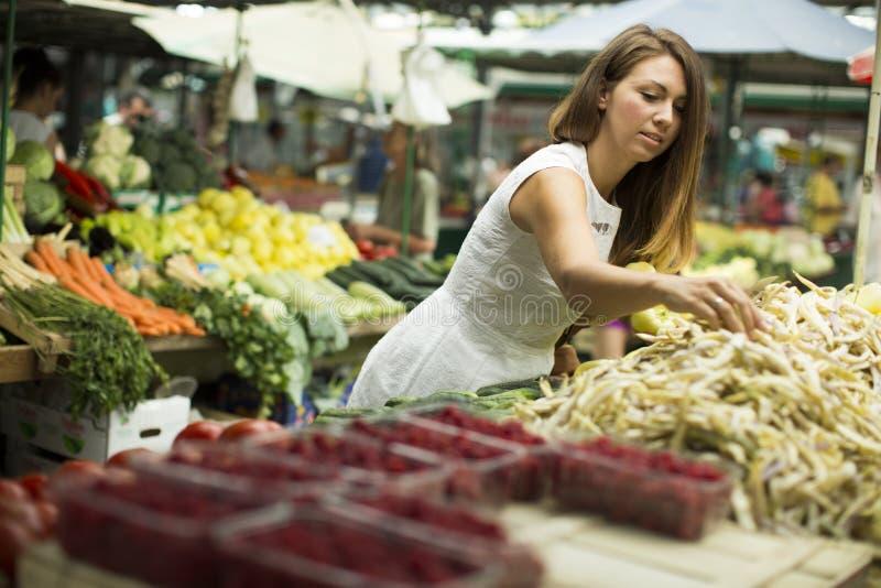 Ung kvinna som väljer den nya grönsaken på marknaden arkivfoton