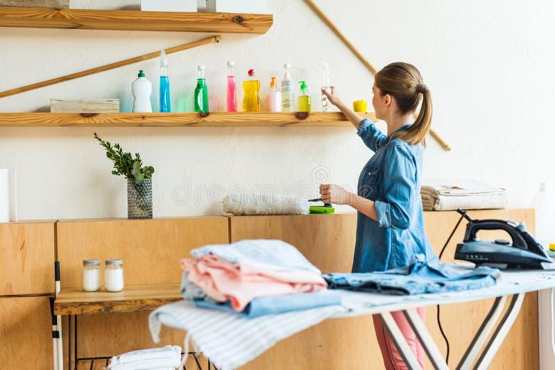 ung kvinna som väljer lokalvårdvätska, medan stryka kläder royaltyfri bild